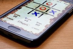 Noughts and crosses on phone. An app on a mobile phone to enable games like noughts and crosses,  shown on the screen, to be played Royalty Free Stock Photos