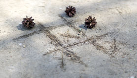Noughts and crosses on the sand. Fir cone Stock Photos