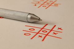 Noughts And Crosses - Tic Tac Toe. Tic Tac Toe known also as Noughts And Crosses and silver pen Stock Images