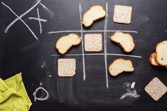Noughts and Crosses Between Useful Harmful Product. Noughts and Crosses Choice Competition Game Between Useful Low-Calorie Product Small Loaf and Harmful Royalty Free Stock Image