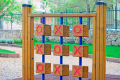 Noughts and crosses. Wooden tic tac toe in a green park Stock Photos