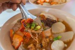 Nouille épicée de Tom yum avec la boule de porc et de viande photographie stock