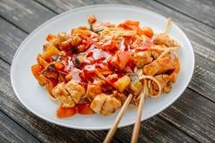 Nouille chinoise en sauce et baguettes aigre-douces sur la table images libres de droits