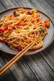 Nouille chinoise en sauce et baguettes aigre-douces sur la table image libre de droits