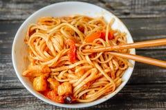 Nouille chinoise en sauce et baguettes aigre-douces sur la table photographie stock