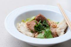Nouille d'oeufs avec du porc et la boulette cuits délicieux dans la cuvette blanche Images libres de droits