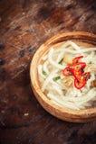 Nouille d'Udon dans la cuvette en bois sur le plancher en bois Image stock