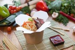 Nouilles chinoises dans la boîte de wok Images stock