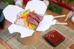 Nouilles chinoises dans la boîte de wok Photo stock