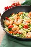 Nouilles de courgette faites sauter avec la tomate-cerise et les crevettes roses dans une casserole photographie stock