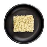 Nouilles de Ramen instantanés crues dans la vue supérieure de cuvette noire d'isolement Photos libres de droits
