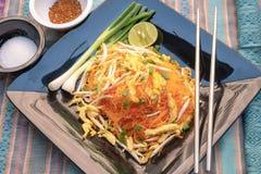 Nouilles de riz faites sauter à feu vif d'un plat noir images libres de droits