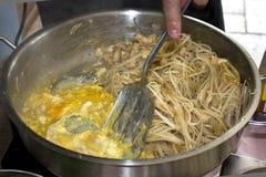 Nouilles de riz de friture de main du ` s d'homme avec le poulet et oeufs dans un grand p image libre de droits
