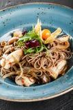 Nouilles de Soba avec les champignons sauvages ? la sauce aigre-doux, aux oignons et aux verts dans le plat sur le fond en pierre photos libres de droits