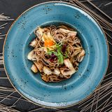 Nouilles de Soba avec les champignons sauvages ? la sauce aigre-doux, aux oignons et aux verts dans le plat sur le fond en pierre photo stock