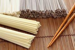Nouilles japonaises avec des baguettes sur la serviette en bambou Image stock