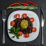Nouilles noires avec des tomates, et sauce à pesto images libres de droits
