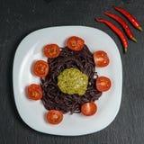 Nouilles noires avec des tomates, et sauce à pesto photographie stock libre de droits