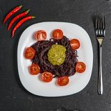 Nouilles noires avec les tomates et la sauce à pesto photographie stock libre de droits