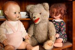 Nounours antique avec des poupées se reposant dans un coffret Photos stock