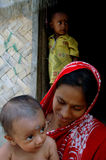 NOURISHED. A VILLAGE WOMAN SPENDS HAPPY MOMENTS WITH HER YOUNGER CHILD IN HER LAP IN FRONT OF HER HOUSE WHILE HER ELDER BOY STANDS AT DOOR Royalty Free Stock Image