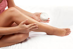 Nourished woman legs with hydrating cream on the skin. On white sheet Stock Photos