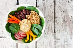 Nourishment lbowl with quinoa, hummus, mixed vegetables, over white wood. Nourishment lunch bowl with quinoa, hummus and mixed vegetables, above view on rustic Royalty Free Stock Photos