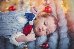 Nourrisson dans le costume se couchant avec la décoration de Noël Image libre de droits