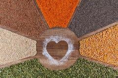 Nourriture avec amour - l'usine a basé le concept diversifié de régime avec les grains et les graines colorés photographie stock libre de droits