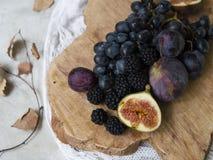 Nourriture bleue et pourpre Mûres, raisins, prunes, myrtilles, figues sur un fond en bois photos libres de droits