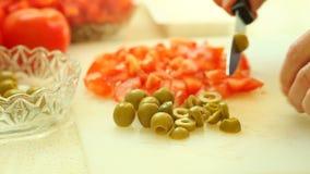 Nourriture découpage en tranches de la coupe avec l'olive verte de couteau de cuisine et la tomate rouge banque de vidéos