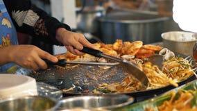 Nourriture délicieuse fraîche de préparation au marché de nuit, mouvement lent Le chef rôtit des fruits de mer dans une casserole banque de vidéos