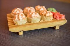 Nourriture d'un plat en bois des petits pains de sushi avec des poissons et ric japonais Photographie stock libre de droits