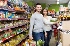 Nourriture de achat de couples heureux dans la boutique Images libres de droits