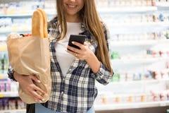Nourriture de achat de sourire de jeune femme dans le supermarché image libre de droits