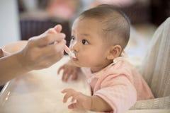 Nourriture de alimentation de b?b? de portrait sur le highchair photo libre de droits