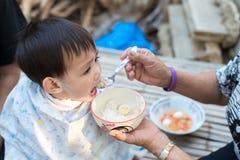 Nourriture de alimentation de bébé garçon asiatique par la grand-mère Photographie stock libre de droits