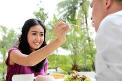 Nourriture de alimentation de belle femme à son ami Images stock