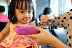 Nourriture de alimentation de fille d'enfant de mère asiatique Photos stock