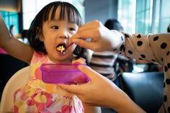 Nourriture de alimentation de fille d'enfant de mère asiatique Photos libres de droits