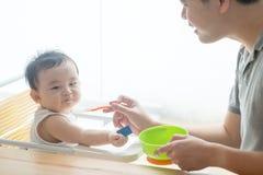 Nourriture de alimentation de solide d'enfant en bas âge de père photo stock