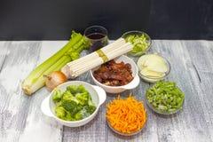 Nourriture de chinois traditionnel - nouilles d'Udon avec du porc et des l?gumes en sauce ? teriyaki sur un conseil en bois Ingr? photographie stock