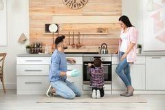 Nourriture de cuisson de famille heureuse en four photographie stock libre de droits