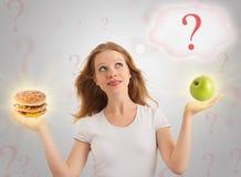Nourriture de fille, saine et malsaine attrayante Photos libres de droits