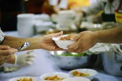Nourriture de part de volontaires aux pauvres pour soulager la faim : Concept de charité photos libres de droits