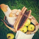Nourriture de pique-nique dans un panier de Wattled sur l'herbe verte Image stock