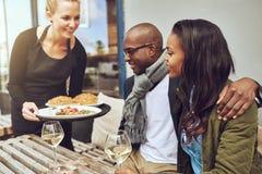 Nourriture de portion de serveuse à un couple africain Photos stock