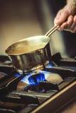 Nourriture de préparation dans le restaurant, sauce dans la tasse en métal, faisant cuire Photo libre de droits