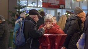 Nourriture de rue, un couple plus âgé mangeant des hamburgers se tenant à un extérieur de table dans la foule banque de vidéos