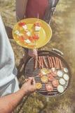 Nourriture de torréfaction de type avec des amis dans la forêt Photographie stock libre de droits